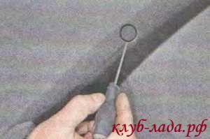 Поддеваем отверткой заглушку винта верхнего крепления обивки