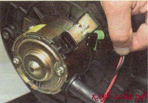 Отжать фиксатор колодки с проводами и отсоединить ее от электродвигателя вентилятора отопителя Калины