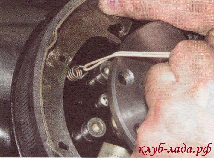 Натягивая пружину, вставляем ее крючок в отверстие колодки