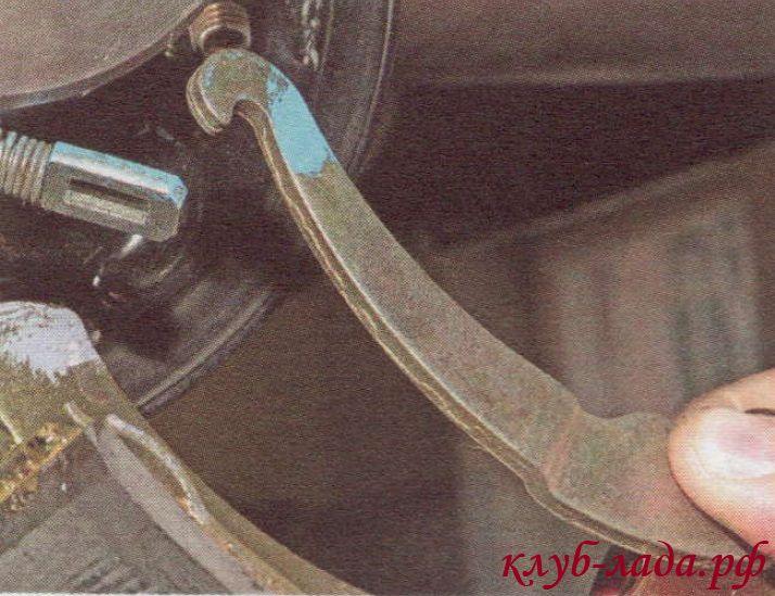 Вывести рычаг ручного привода колодок из отверстия наконечника троса стояночного тормоза