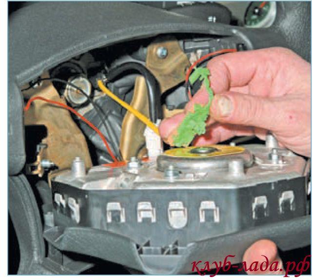 Поднять фиксатор колодки с проводами, и отсоединить провода от подушки