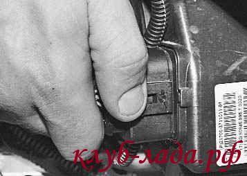 Отжать фиксатор и отсоединить от фары колодку жгута проводов