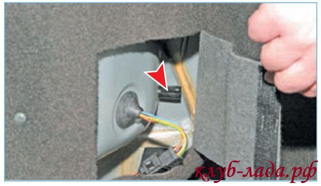 Отогнуть клапан обивки внутри багажника