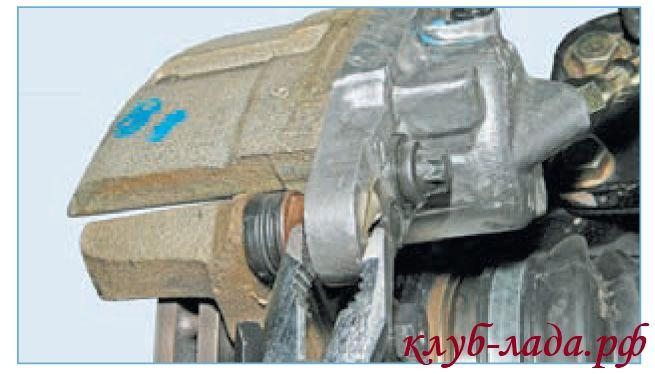 Отогнуть края стопорной пластины болта крепления цилиндра суппорта приоры